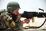 An Afghan National Army soldier fires an M240B machine gun during a live-fire exercise .